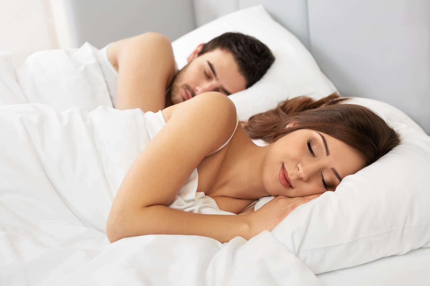 Young happy couple sleeping in bed