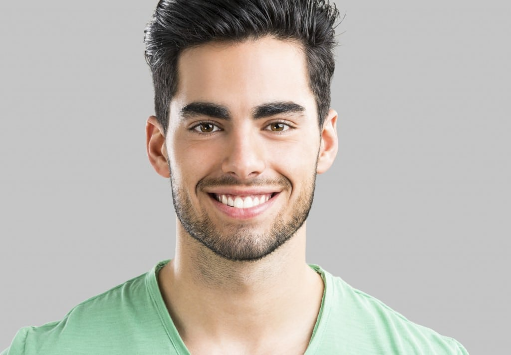 Portrait of handsome young man smiling, isolated on gray background