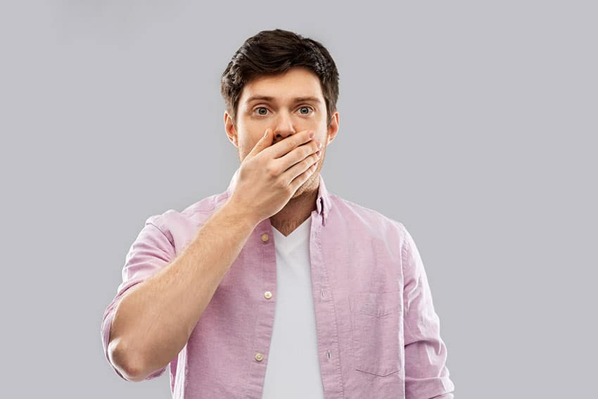 man covering his mouth due to bad breath